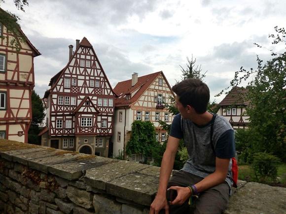 Lino sentado numa mureta na cidade onde morava, olhando casas em estilo alemão Blog Vem Por Aqui
