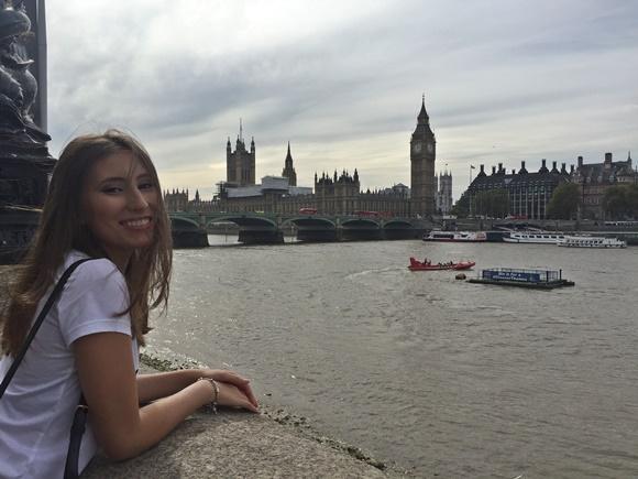 Elisa diante debruçada na mureta diante do Tâmisa com o Big Ben ao fundo, em Londres Blog Vem Por Aqui