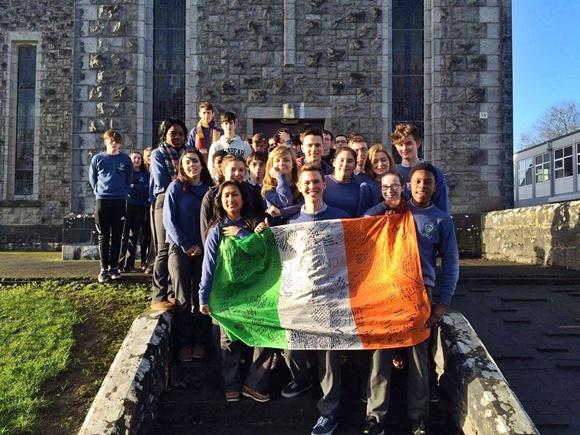 Tiago e os colegas da aula de Química em frente à escola segurando uma bandeira Blog Vem Por Aqui