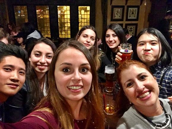 Amigos e Érika sorrindo para uma selfie num pub Blog Vem Por Aqui