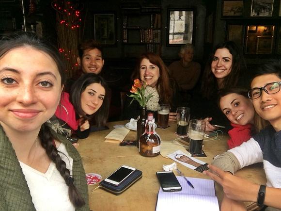 Érika e amigos sentados numa mesa de bar com telefones e cervejas sobre a mesa Blog Vem Por Aqui