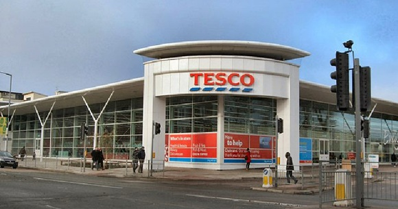 Parte externa do supermercado com entrada arredondada com nome em cima e lateral de vidro Blog Vem Por Aqui