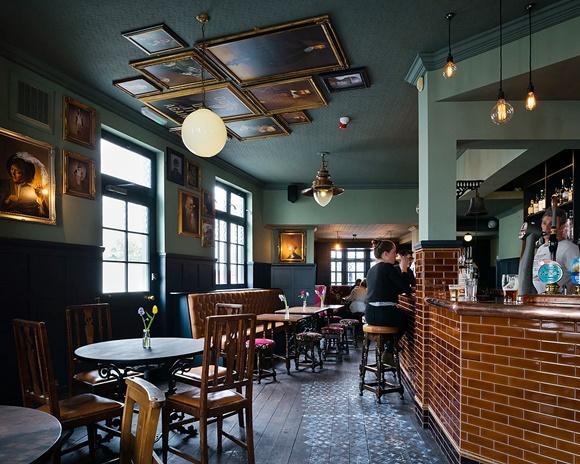 Parte interna do bar com mesas e bancos em frente ao bar Blog Vem Por Aqui