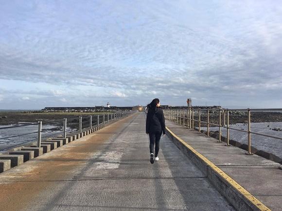 Clara andando de costas num longo caminho de concreto com nuvens ao fundo Blog Vem Por Aqui