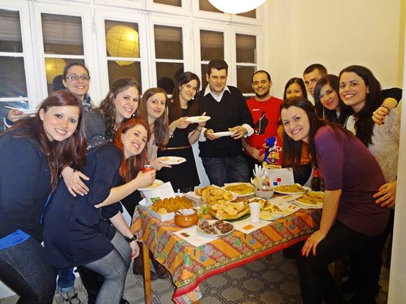 Érika e a turma dela do máster em volta de uma mesa cheia de comidas de cada país Blog Vem Por Aqui