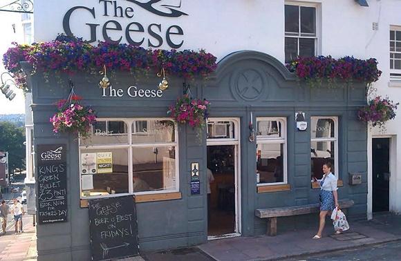 Frente do The Geese com flores no topo da parede e mulher passando em frente Blog Vem Por Aqui