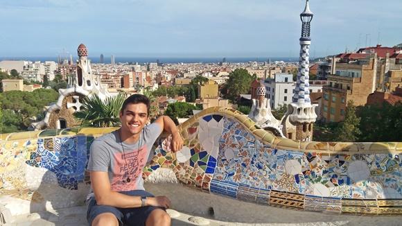 Guilherme no Parc Guell sentado num banco de mosaico colorido Blog Vem Por Aqui