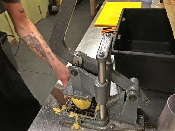 Mão colocando batata na máquina de picar Blog Vem Por Aqui