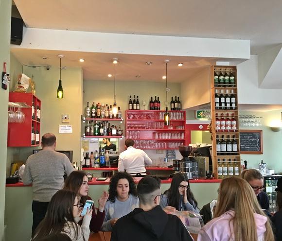 Pessoas sentadas numa mesa diante do bar Blog Vem Por Aqui