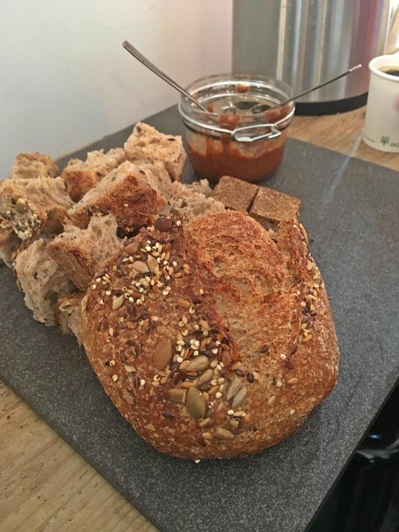 Pão rústico em cima de uma mesa e pote de manteiga de Amendoim