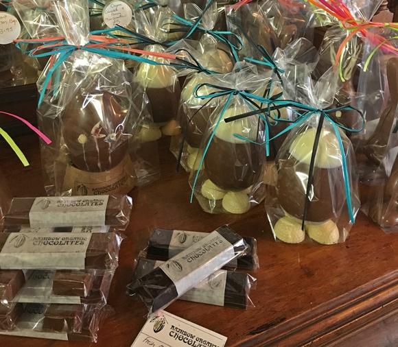Ovos e barras de chocolate em cima de um móve de madeira Blog Vem Por Aqui