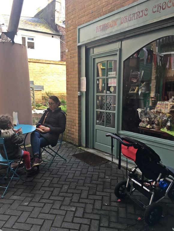 Mãe e filha em frente à loja, sentadas, Blog Vem Por Aqui