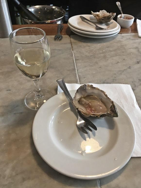 Prato branco com ostra e, em frente, tacinha de vinho Blog Vem Por Aqui