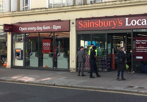 Frente do supermercado com pessoas entrando na porta. Em cima, placa com nome e outro letreiro antes dizendo (em inglês) que abre todo dia de 6h às 23h Blog Vem Por Aqui