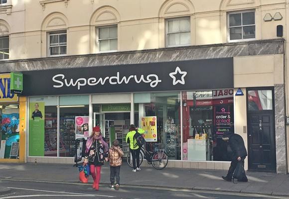 Frente da Superdrug com nome da loja acima e estrela que faz parte da marca ao lado Blog Vem Por Aqui