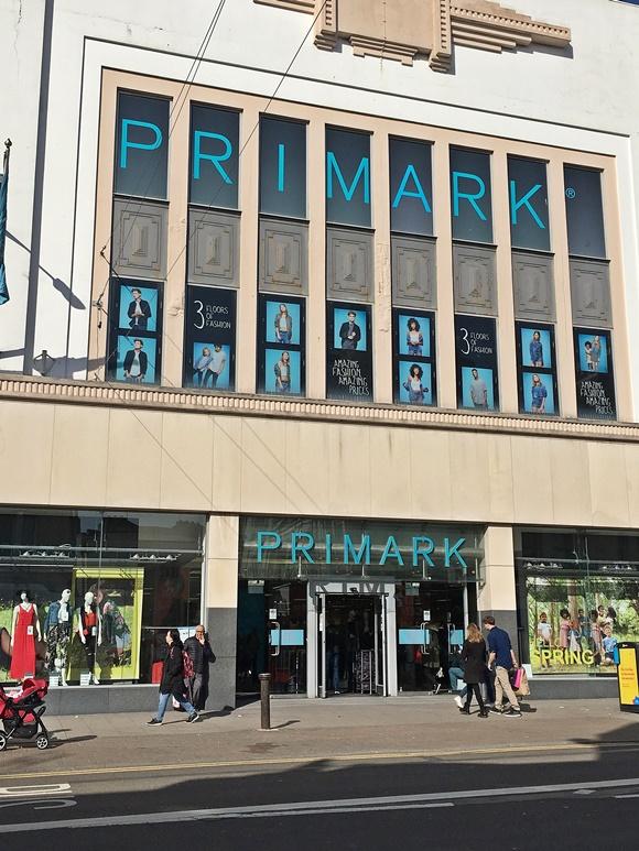 Fachada da loja com nome acima da entrada e no alto do prédio com uma letra adesivada em cada janela Blog Vem Por Aqui