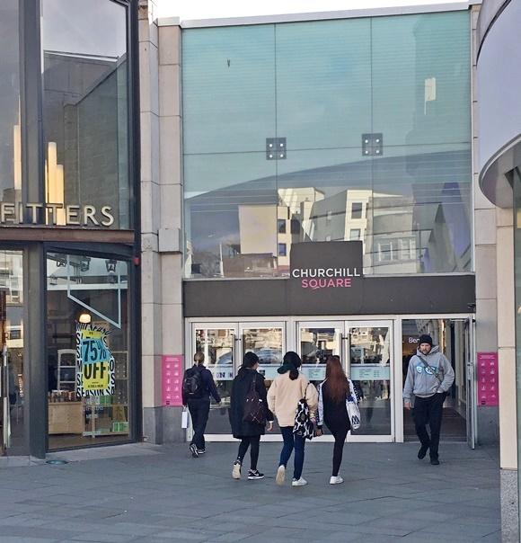 Entrada do shopping com homem saindo e quatro jovens entrando Blog Vem Por Aqui