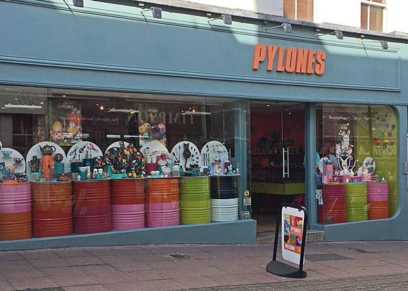 Frente da loja com vitrines de vidro com tonéis coloridos e produtos expostos em cima Blog Vem Por Aqui