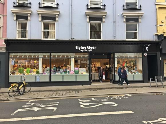 Frente da loja com bicicleta parada no canto esquerdo e pessoas passando no direito Blog Vem Por Aqui
