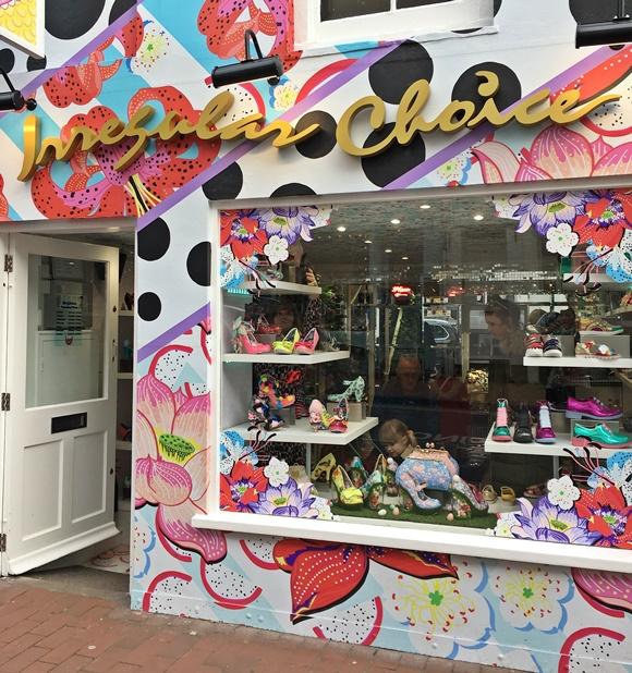 Fachada toda colorida com nome da loja no alto e vitrine de vidro, exibindo sapatos coloridos Blog Vem Por Aqui