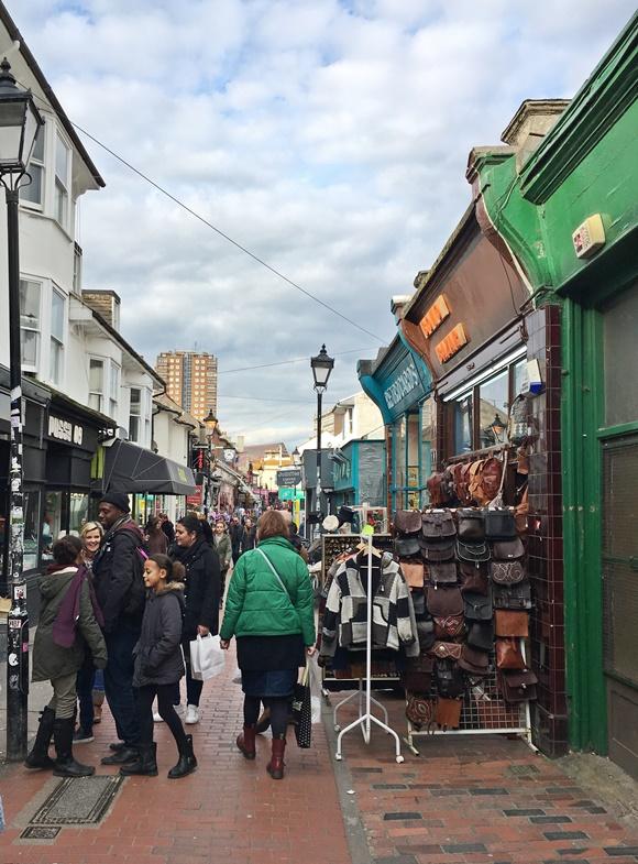 Pessoas andando no meio da rua com barraquinha vendendo artigos de couro no começo Blog Vem Por Aqui