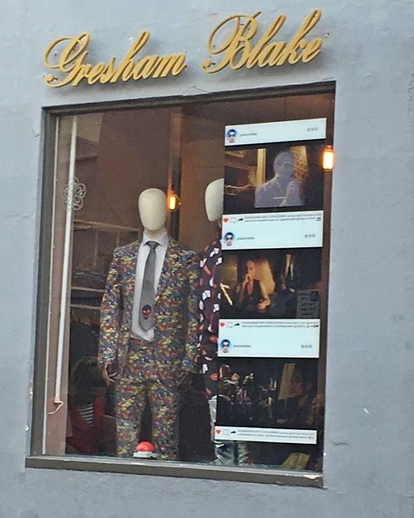 Vitrine de vidro exibindo terno todo colorido e gravata com caveira na ponta Blog Vem Por Aqui