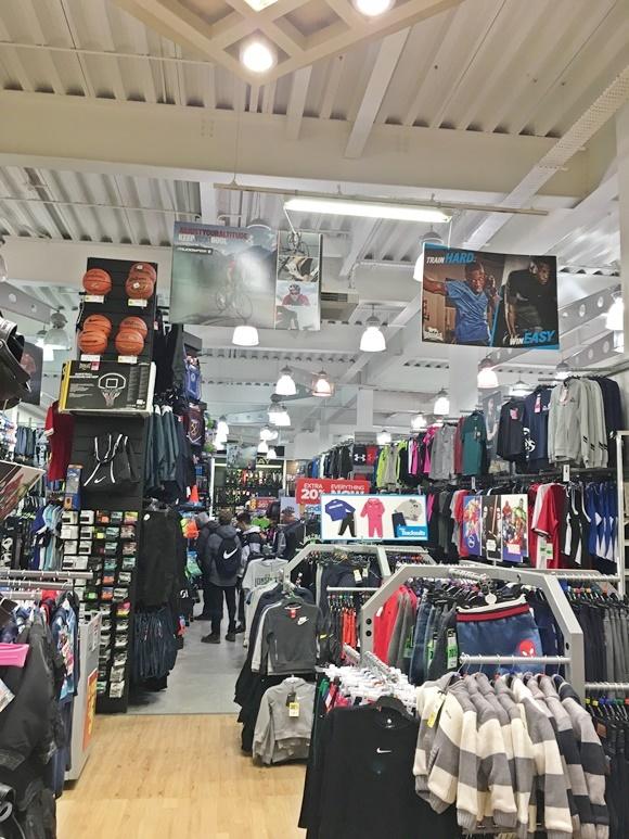 Parte interna da loja com imensos expositores cheios de roupa e araras com mais produtos no meio Blog Vem Por Aqui