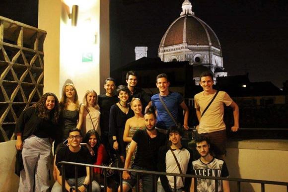 Paula no meio de um grupo de pessoas no topo de um prédio com o Duomo aparecendo ao fundo Blog Vem Por Aqui