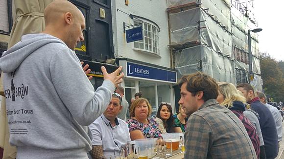 Robert em frente a um grupo de clientes sentados numa mesa com cervejas à frente dando explicações no tour Blog Vem Por Aqui