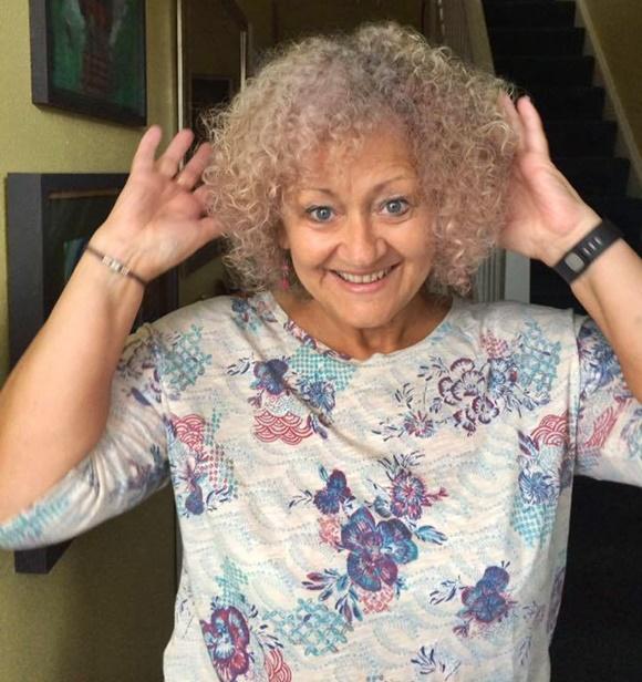 Leia, senhora de olhos azuis e cabelo cacheados brancos, com as mãos para trás da cabeça, sorrindo para a câmera Blog Vem Por Aqui