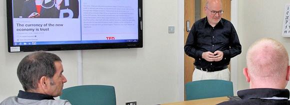 Professor diante do quadro com uma palestra do TED e alunos mais velhos de costas para a câmera Blog Vem Por Aqui