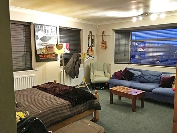 Quarto com cama de casal, mesinha de madeira no meio, diante de sofá de três lugares, sofá individual no canto, abajur e janela grande ao fundo Blog Vem Por Aqui