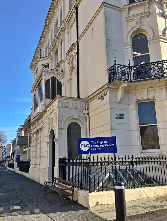 Prédio do ELC em Brighton com placa na lateral com o nome da escola e a cidade Blog Vem Por Aqui