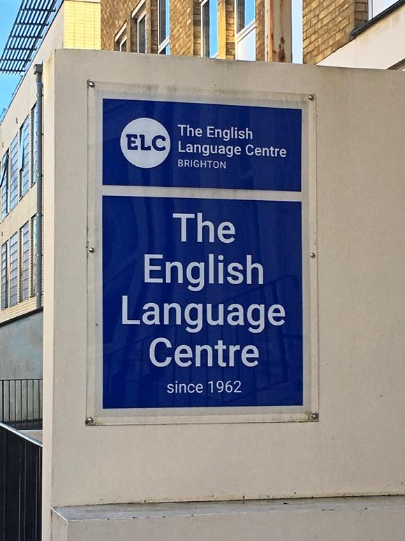 Placa com o nome da escola escrito menor em cima e repetido abaixo com a frase since 1962 no final Blog Vem Por Aqui