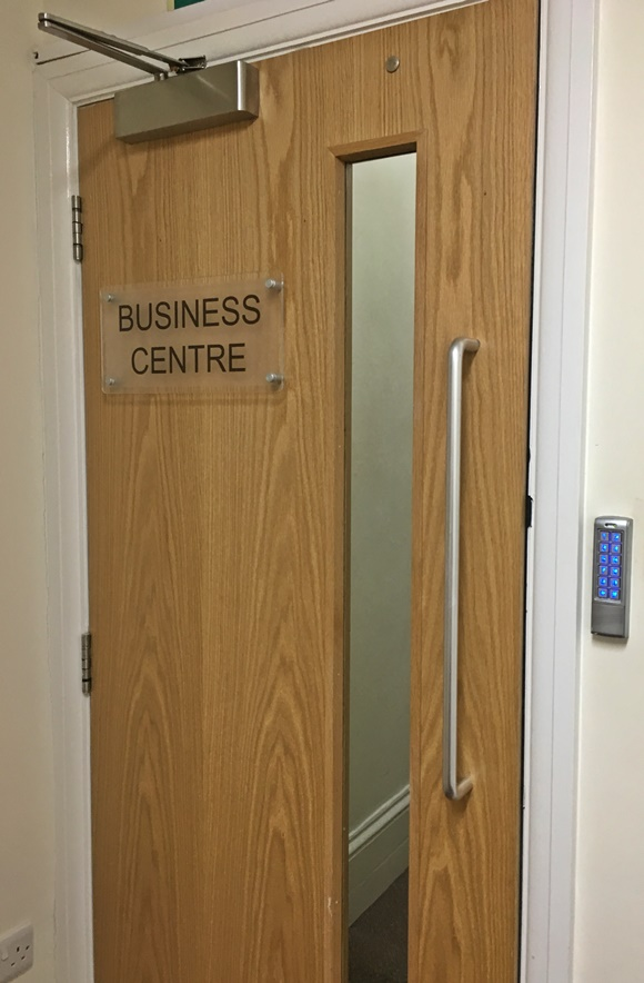 Porta com placa escrita Business Centre e, ao lado, pequeno painel com números para os alunos digitarem a senha Blog Vem Por Aqui
