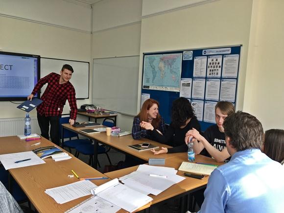 Érika e colegas na sala de aula, um deles está em pé diante do quadro, curvado, com uma prancheta na mão, os demais estão sentados Blog Vem Por Aqui