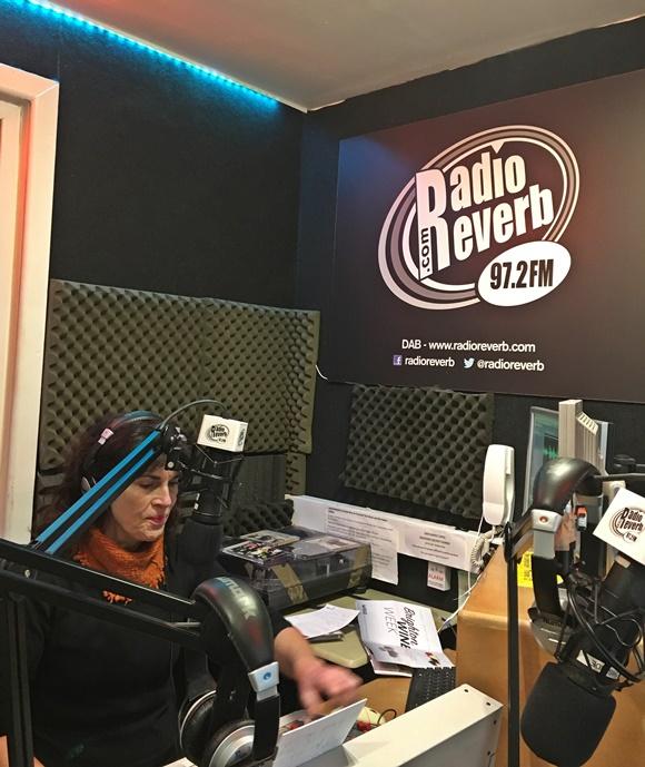Karen com fones de ouvido, sentada no estúdio da rádio, diante do microfone Blog Vem Por Aqui