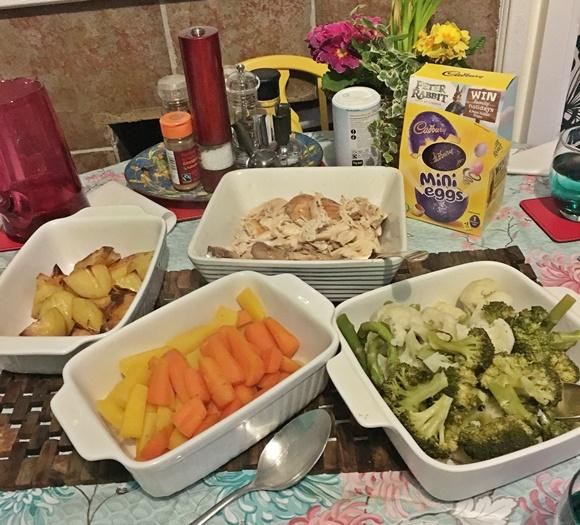 Mesa com travessas com vegetais e frango e, ao fundo, caixa com ovo de páscoa Blog Vem Por Aqui