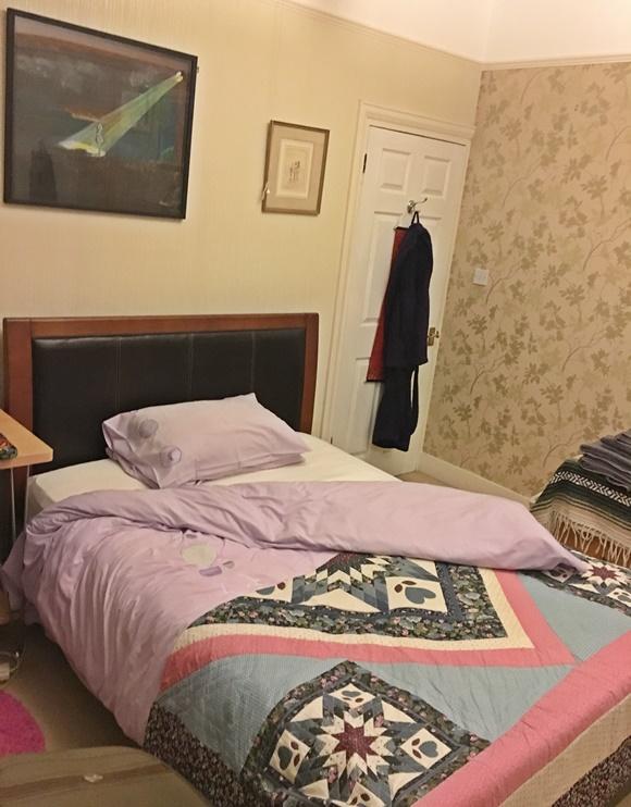 Cama com colcha dobrada na metade e travesseiro, ao fundo porta do quarto com roupão pendurado e quadro na cabeceira Blog Vem Por Aqui