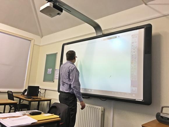 Professor de costas para a turma, escrevendo no quadro Blog Vem Por Aqui