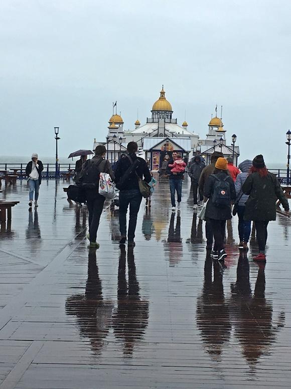 Pessoas andando na chuva em direção ao pier de Eastbourne Blog Vem Por Aqui