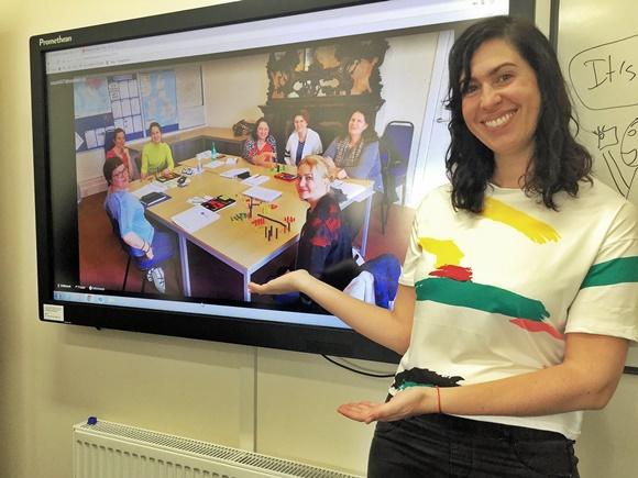 Laura com os braços indicando o quadro ao lado com a imagem da professora e alunos sentados numa mesa retangular Blog Vem Por Aqui