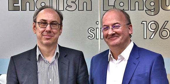 Phil ao lado de Peter, os dois sorrindo em frente a um vidro com o nome da escola e o ano de fundação adesivados Blog Vem Por Aqui