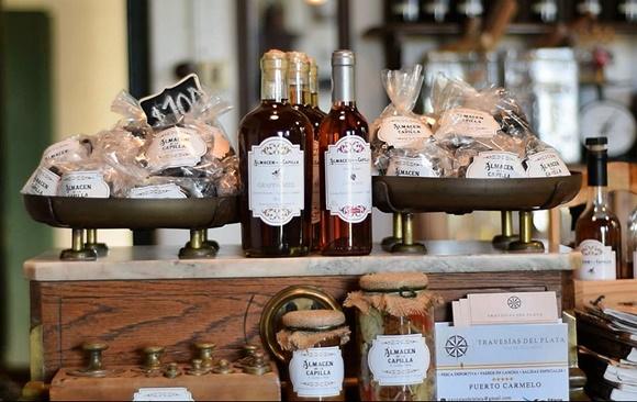 Produtos em cima de uma balança antiga feita de madeira e mármore, há vidros de vinhos, compotas e saquinhos de biscoitos Blog Vem Por Aqui