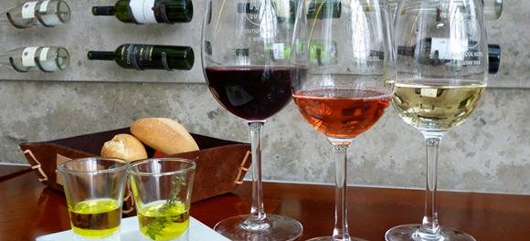 Taças com três tipos de vinho e dois copinhos pequenos com azeite, cesta de pães ao fundo Blog Vem Por Aqui