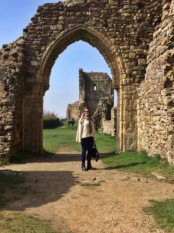 Paloma em frente a um portal de pedras e outras ruínas Blog Vem Por Aqui