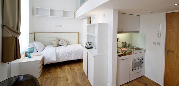Quarto com cama, mesa de cabeceira e estante que fica na parede divisória com a cozinha Blog Vem Por Aqui