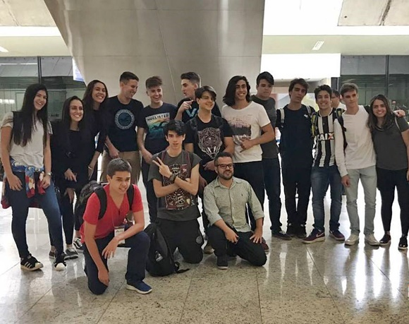 Alunos que viajaram com a Central no aeroporto com Fernando ajoelhado diante deles Blog Vem Por Aqui