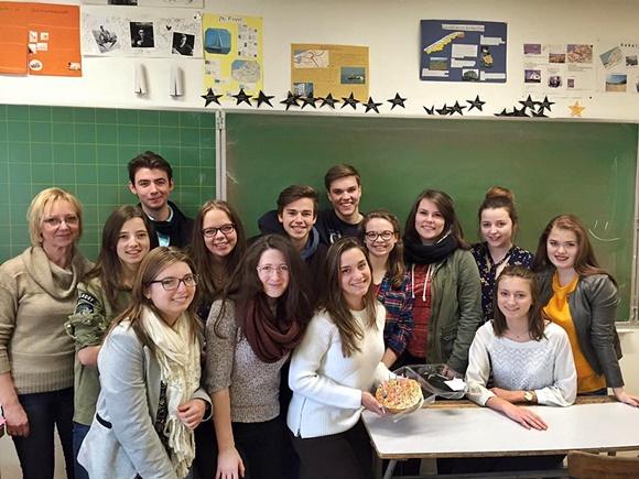 Clara na sala de aula, segurando um bolo, no dia do aniversário com colegas e a professora em volta Blog Vem Por Aqui