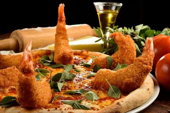 Pizza com camarões grandes empanados em pé sobre a massa